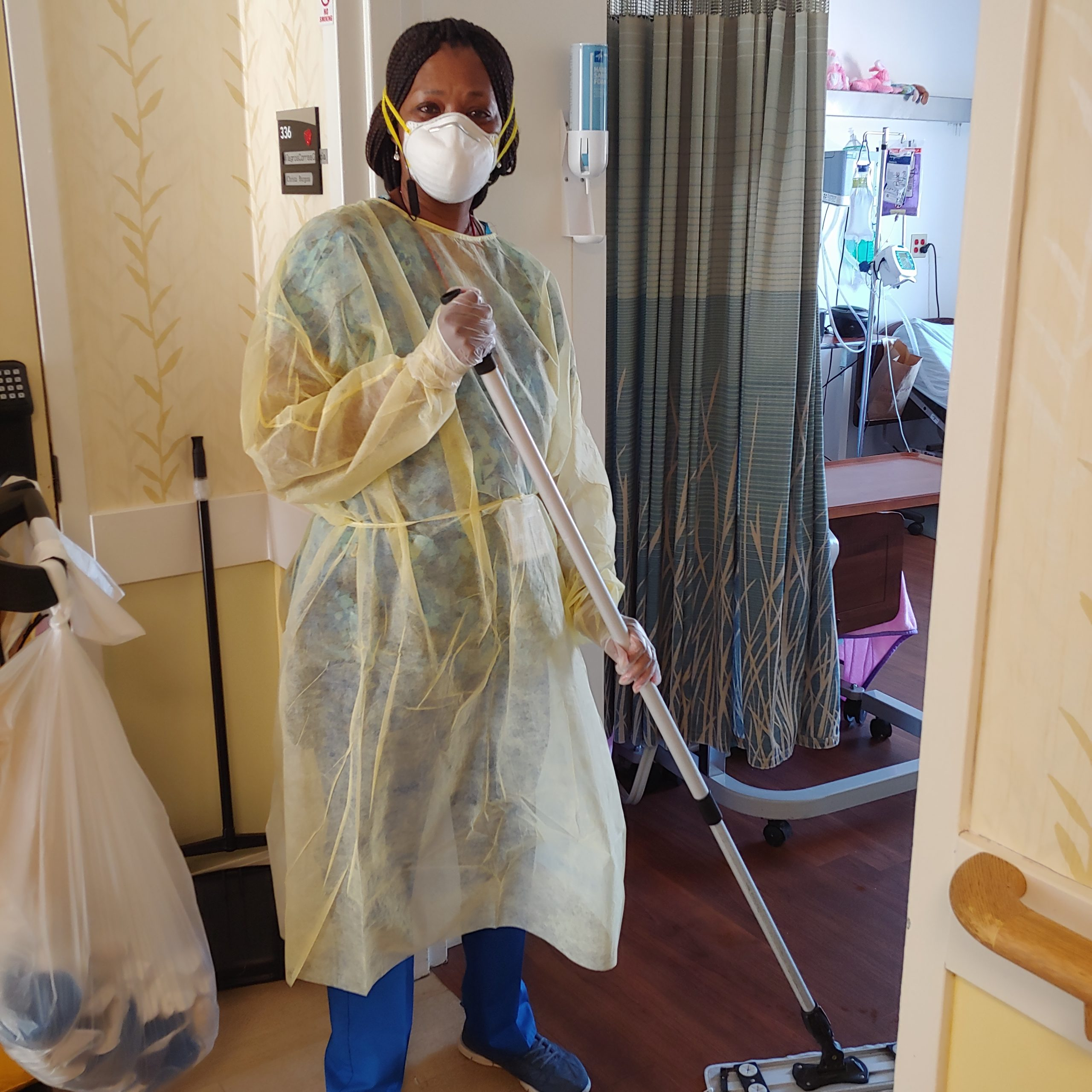 Housekeeping staff wearing PPE  in compliance with COVID-19 infection control and cleaning floor