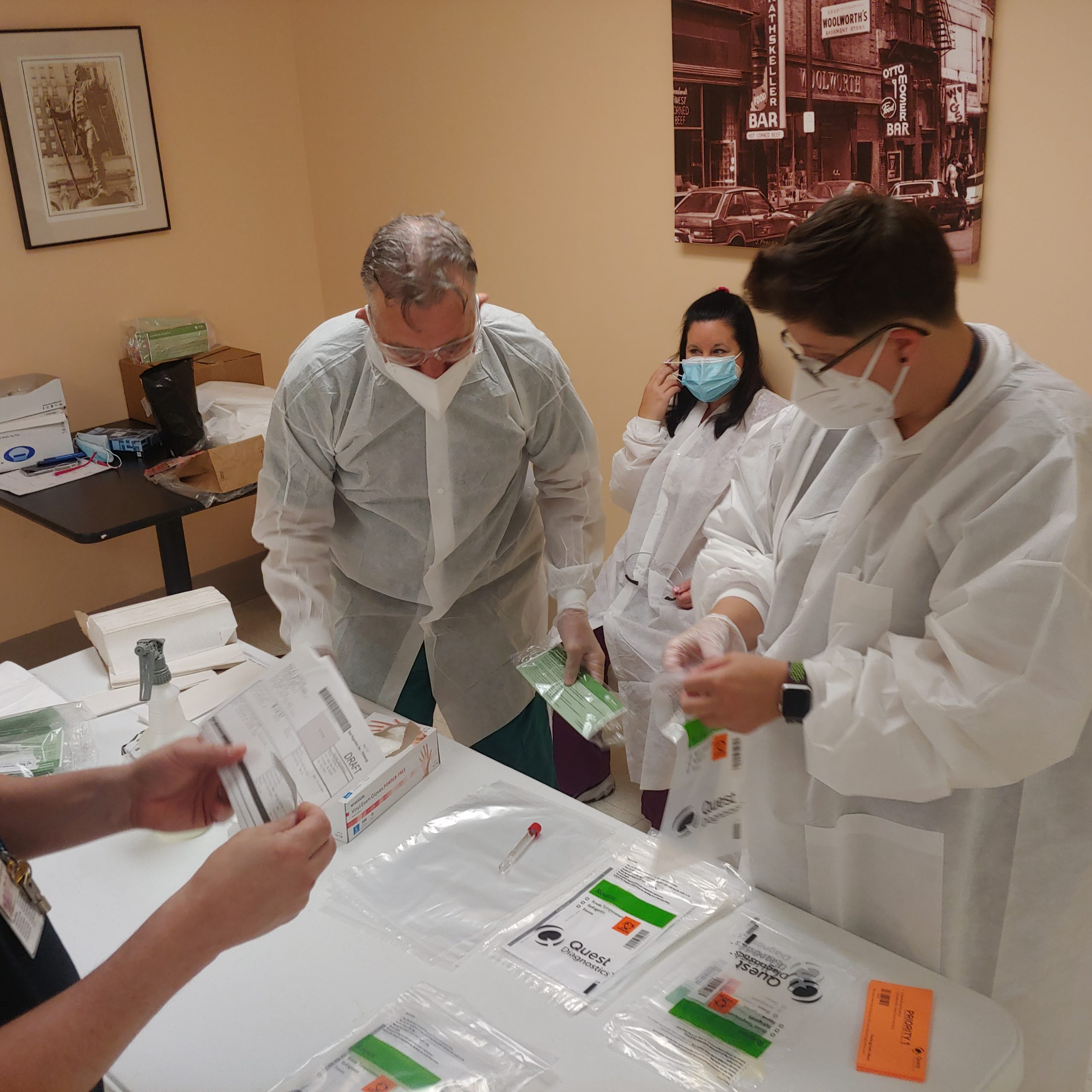 Staff members in PPE  in compliance with COVID-19 infection control preparing COVID-19 testing kits