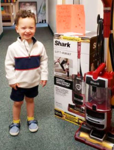 Boy standing next to donation to child enrichment center